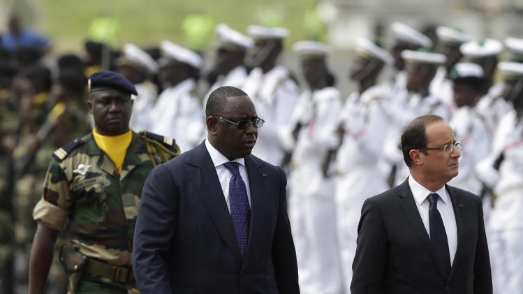 French President Francois Hollande, right, and Senegalese counterpart Macky Sall walk past an honor guard as Hollande arrives at the airport in Dakar, Senegal, Friday, Oct. 12, 2012. Hollande was on a one-day visit to Senegal Friday, en route to Kinshasa, Congo for the Francophonie Summit. (AP Photo/Rebecca Blackwell)