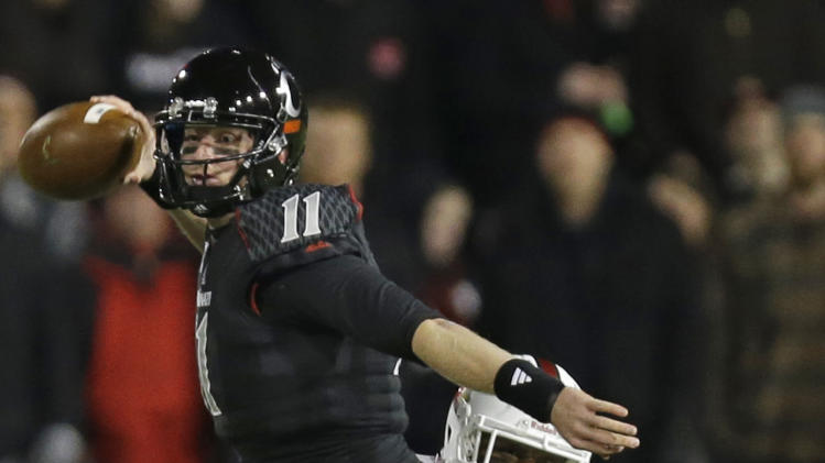 Cincinnati quarterback Brendon Kay (11) is hit by Louisville linebacker Preston Brown (2) as he passes the ball in the first half of an NCAA college football game on Thursday, Dec. 5, 2013, in Cincinnati. (AP Photo/Al Behrman)