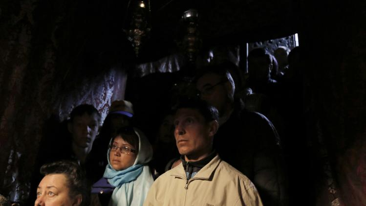 Tourists stand in the Grotto at the Church of Nativity ahead of Christmas in Bethlehem