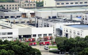 Firefighter trucks are seen next to a damaged building after an explosion at a factory in Zhoushan