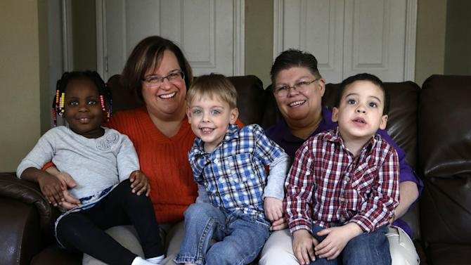 """FILE- In a March 5, 2013 photo, April DeBoer, second from left, sits with her adopted daughter Ryanne, 3, left, and Jayne Rowse, fourth from left, and her adopted sons Jacob, 3, middle, and Nolan, 4, right, at their home in Hazel Park, Mich. A judge is refusing to dismiss a lawsuit by the two women challenging Michigan's ban on gay marriage and joint adoptions by same-sex couples. Detroit federal Judge Bernard Friedman says Rowse and DeBoer """"are entitled to their day in court."""" (AP Photo/Paul Sancya, file)"""