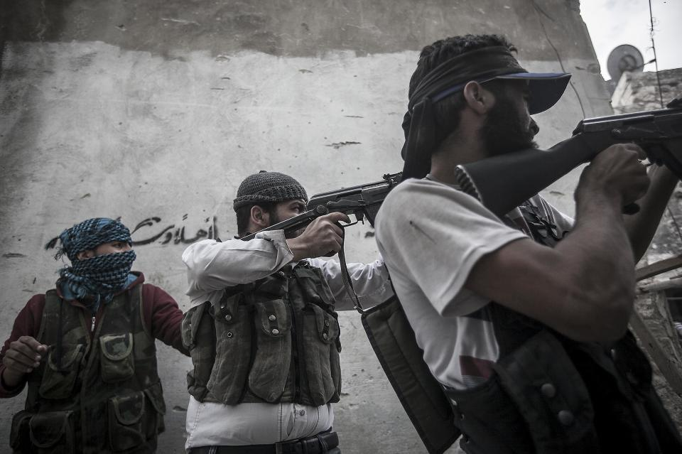 In this Wednesday, Oct. 24, 2012 photo, rebel fighters belonging to the Liwa Al Tawhid group shoot towards government troops during clashes at the Moaskar front line, one of the battlefields in Karmal Jabl neighborhood, in Aleppo Syria. (AP Photo/Narciso Contreras).