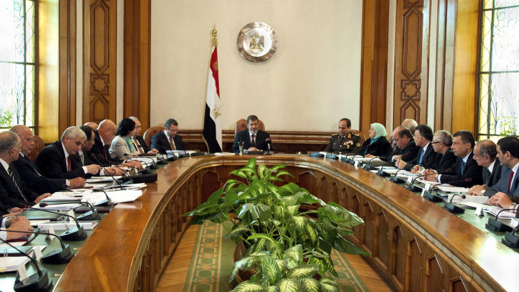 FILE - In this Sunday Jan. 6, 2013 file image released by the Egyptian Presidency, President Mohammed Morsi, center, meets with his cabinet including 10 new ministers after their swearing in at the presidential palace in Cairo, Egypt. As Egypt begins the latest round of talks with the International Monetary Fund for a $4.8 billion loan, the government says it will boost international confidence in its economy. However, critics question whether the president's Muslim Brotherhood group has the ability to carry out unpopular austerity measures ahead of crucial parliamentary elections that will take place in the coming months. (AP Photo/Egyptian Presidency, File)