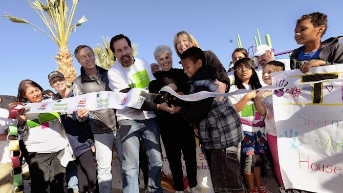 IMAGE DISTRIBUTED FOR HUMANA-Volunteers cut a ceremonial ribbon after building a one-of-kind, multi-generational playground at the Boys & Girls Clubs of Coachella Valley, on Saturday, Jan. 12, 2013, in Desert Hot Springs, Calif. Nearly 400 volunteers joined The Humana Foundation, the philanthropic arm of Humana, Inc., one of the nation's leading health care companies; KaBOOM!, a national non-profit organization that has built more 2,200 playgrounds; the Boys & Girls Clubs of Coachella Valley and the City of Desert Hot Springs to build the playground in just six hours. The playground build is one of many wellness-focused activities taking place leading up to the 2013 Humana Challenge PGA TOUR golf tournament, which will be held Jan. 14-20, 2013, in La Quinta, Calif. The build is a direct result of people who wore Humana pedometers and logged their steps during the 2012 Humana Challenge Walkit program, in which every step counted toward the donation made by the Humana Foundation (Gabriel Acosta / AP Images for Humana).