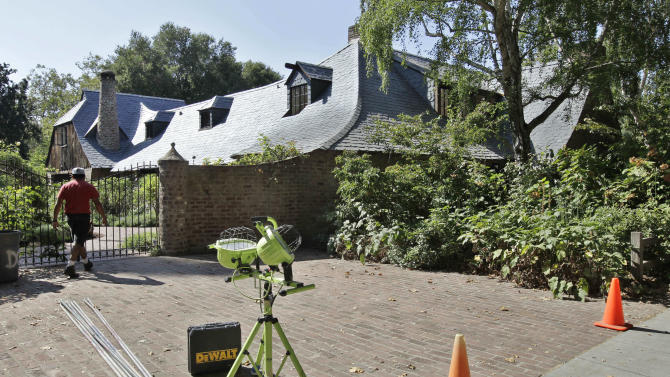 A worker walks into the house of Steve Jobs in Palo Alto, Calif., Friday, Aug. 17, 2012. Kariem McFarlin, 35, was arrested on Aug. 2, 2012 and accused of breaking into the Jobs home and stealing iPods, Macs, jewelry and Jobs' wallet on July 17, 2012, investigators said. (AP Photo/Paul Sakuma)