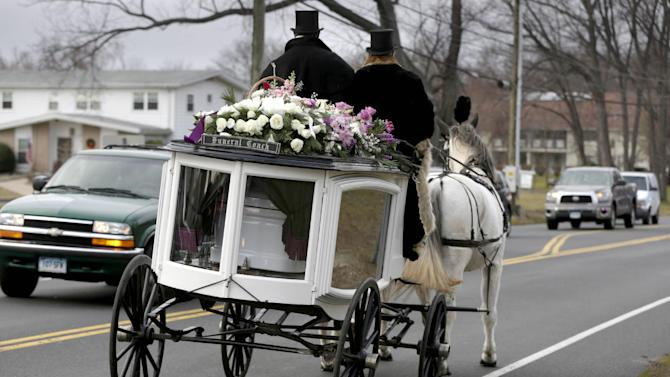 A horse drawn carriage carrying the body of Anna Grace Marquez-Greene leaves the church after her funeral in Bloomfield, Conn., Saturday, Dec. 22, 2012.  Marquez-Greene, 6,  was killed when gunman Adam Lanza opened fire at Sandy Hook Elementary School last week, killing 26 people, including 20 children, before killing himself. (AP Photo/Seth Wenig)