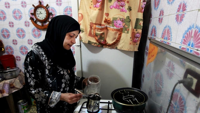 In this Friday, May 24, 2013 photo, Lebanese Sahar Ashrafiyeh, 45, prepares coffee at her house, in the northern port city of Tripoli, Lebanon. Ashrafiyehs fled the neighborhood in 1985, after her husband Mahmoud was shot in the leg during a fight with people from Jabal Mohsen, she said. The family settled in Germany, but returned in 1992. Fighting between Bab Tabbaneh and Jabal Mohsen, which goes back to Lebanon's civil war, has become more frequent since the start of the Syrian conflict in 2011, with the neighborhoods backing opposite sides. And the latest round over the past week has been the longest yet and has left tens dead and hundreds wounded, the highest toll so far. (AP Photo/Bilal Hussein)