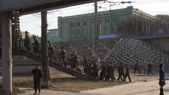 "FILE - In this Friday, April 12, 2013 file photo, North Korean soldiers climb stairs on a street overpass in Pyongyang, North Korea. Enemy capitals, North Korea said, will be turned ""into a sea of fire."" North Korea's first strikes will be ""a signal flare marking the start of a holy war.""  Pyongyang's nuclear arsenal is ""mounted on launch pads, aimed at the windpipe of our enemies."" And it's not all talk. The profoundly isolated, totalitarian nation has launched two rockets over the past year. But there is also a logic behind North Korea's behavior, a logic steeped in internal politics, one family's fear of losing control and the ways that a weak, poverty-wracked nation can extract concessions from some of the world's most fearsome military powers. (AP Photo/David Guttenfelder, File)"