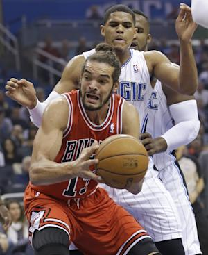 Chicago Bulls' Joakim Noah, front, looks to go up for a shot off a rebound in front of Orlando Magic's Tobias Harris during the first half of an NBA basketball game in Orlando, Fla., Wednesday, Jan. 15, 2014. (AP Photo/John Raoux)