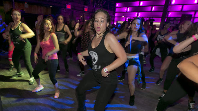 Teena-Marie DiBartolo, center, and her mother Myra DiBartolo, left, participate in a Vixen Workout fitness concert, at the Highline Ballroom, in New York, Saturday, July 26, 2014. Former Miami Heat dancer Janet Jones created the Vixen Workout two years ago after she lost her job as a financial assistant and her high-energy routine has caught on in New York and other cities. (AP Photo/Richard Drew)