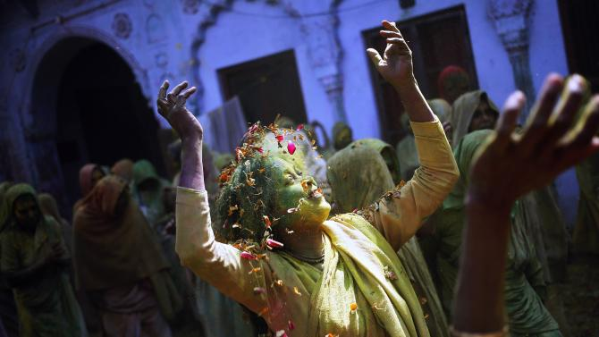 A widow daubed in colours dances in the Holi celebrations organised by non-governmental organisation Sulabh International at a widows' ashram at Vrindavan