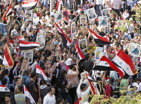 Supporters of Syrian President Bashar al-Assad's wave flags and hold pictures of al-Assad during a rally at al-Sabaa Bahrat square in Damascus