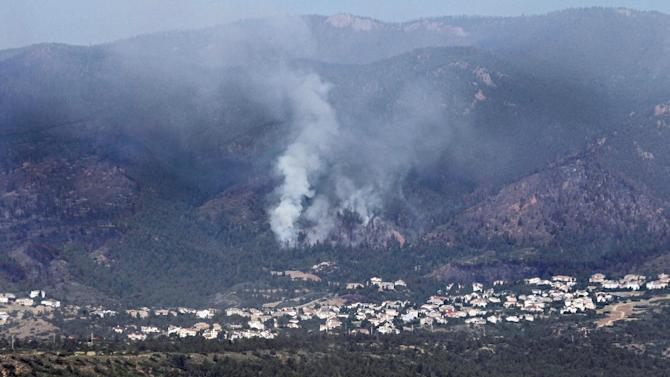 The Waldo Canyon wildfire burns on the side of a mountain above a housing development at the U.S. Air Force Academy north of Colorado Springs, Colo., on Thursday, June 28, 2012. Hundreds of homes have been destroyed by an out-of-control Colorado wildfire that has forced more than 30,000 people to flee, officials said Thursday.  (AP Photo/Ed Andrieski)