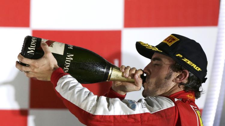 Ferrari Formula One driver Alonso drinks champagne on the podium after the Singapore F1 Grand Prix in Singapore