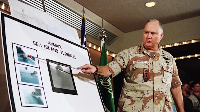 FILE - In this Jan. 27, 1991 file photo, U.S. Army Gen. Norman Schwarzkopf points to row of photos of Kuwait's Ahmadi Sea Island Terminal on fire after a U.S. attack on the facility. Schwarzkopf died Thursday, Dec. 27, 2012 in Tampa, Fla. He was 78. (AP Photo/Laurent Rebours, File)
