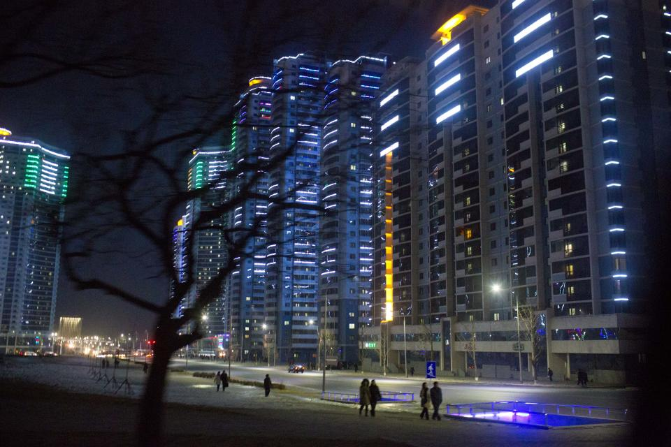In this Feb. 21, 2013 photo, North Kroeans walk on a sidewalk under brightly lit apartment buildings on the new Changjon Street in Pyongyang, North Korea. (AP Photo/David Guttenfelder)