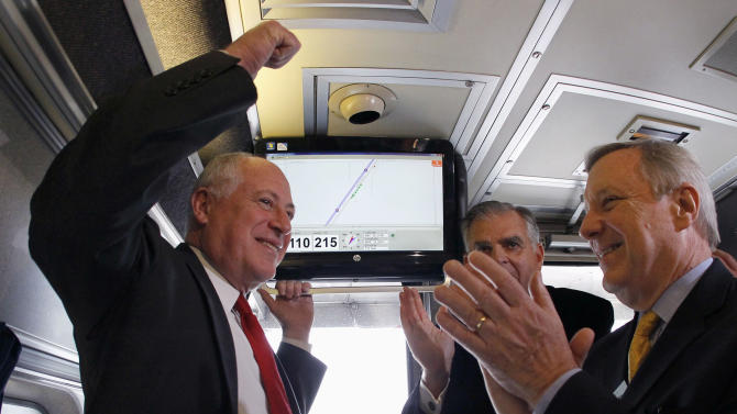 FILE - In this Oct. 19, 2012 file photo, Gov. Pat Quinn, left, U.S. Transportation Sec. Ray LaHood, center, and Sen. Dick Durbin, D-Ill., celebrate in Pontiac, Ill., after the Amtrak train they are riding reached 110 mph during a test run between Pontiac and Dwight, Ill. Hundreds of Midwest manufacturers stand to benefit from a web of high-speed passenger rail routes emerging from Chicago's rail hub, according to a report released by an environmental policy group that has fought to defend the use of billions in taxpayer money on such projects.  (AP Photo/Charles Rex Arbogast, File)
