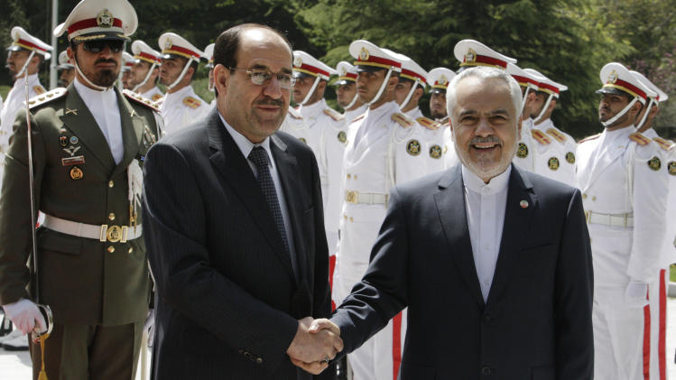 Iraqi Prime Minister Nouri al-Maliki, center, shakes hands with Iranian Vice-President Mohammad Reza Rahimi during his official arrival ceremony in Tehran, Iran, Sunday, April 22, 2012. (AP Photo/Vahid Salemi)