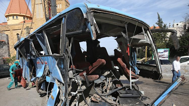 A worker, left, removes a damaged seat from a destroyed Syrian bus that was headed to the Lebanese capital, Beirut, when an accident occurred in the Kahhaleh region of Lebanon, Friday March 15, 2013. Officials say at least eight Syrians were killed and 29 were injured when the bus they were traveling in from Syria overturned in the mountains in central Lebanon. (AP Photo/Hussein Malla)