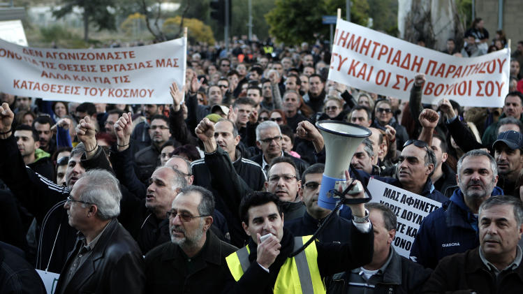 "Bank employees protest outside the ministry of finance on Saturday, March 23, 2013. Thousands of bank employees took part in a protest that ended outside the Cypriot parliament. Politicians in Cyprus were racing Saturday to complete an alternative plan raising funds necessary for the country to qualify for an international bailout, with a potential bankruptcy just three days away. Banner at left reads: We fight not only for our jobs but also for people's savings"" and banner at right reads: ""Dimitriadis resign, you and your consultants"". (AP Photo/Petros Giannakouris)"
