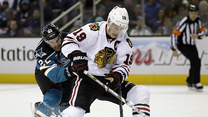 Chicago Blackhawks center Jonathan Toews (19) controls the puck in front of San Jose Sharks defenseman Dan Boyle during the first period of an NHL hockey game in San Jose, Calif., Tuesday, Feb. 5, 2013. (AP Photo/Marcio Jose Sanchez)