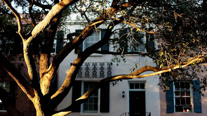 In this Feb. 21, 2011 photo, the setting sun casts a ray of light against a tree in the historic district of Savannah, Ga. A proposal to roll out double-decker buses on the streets of historic downtown Savannah has residents complaining the change would amount to a tourism overload. Two Boston businessmen are lobbying Savannah City Hall to end a 17-year ban on double-decker buses in the downtown historic district of Georgia's oldest city. The city's Downtown Neighborhood Association is opposing the change. Its members say the buses would risk collisions with low-hanging tree limbs and would turn passengers into Peeping Toms capable of peering into second-story windows. (AP Photo/David Goldman)