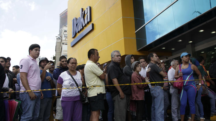 Shoppers wait outside to come in a Daka appliance store in Caracas, Venezuela, Saturday, Nov. 9, 2013. In a bid to bring down prices that have jumped in tandem with demand for dollars on the black market, Venezuela's President Nicolas Maduro on Wednesday tightened controls on currency transactions. With hard-fought municipal elections approaching next month, he also ordered the military to shut down businesses found hoarding products or speculating on prices. (AP Photo/Ariana Cubillos)