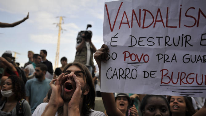 A protester yells at a police helicopter in Rio de Janeiro, Brazil June 16, 2013. Brazilian police have dispersed a small protest against a public transport fare hike that broke out in front of Rio de Janeiro's Maracana stadium ahead of the Mexico-Italy soccer match during the Confederations Cup. (AP Photo/Nicolas Tanner)