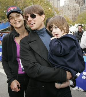 FILE - In this Nov. 4, 2007 file photo, actress Katie Holmes, husband Tom Cruise, center, and their daughter Suri pose for a photograph after Holmes finished running the New York City Marathon in New York. Actress Kristen Bell is leading a movement aimed at reducing the marketplace for paparazzi images of celebrity kids taken without parents' consent, and she's using 8-year-old Suri as an example: a child chased by cameras, with no choice in the matter. (AP Photo/Kathy Willens, file)