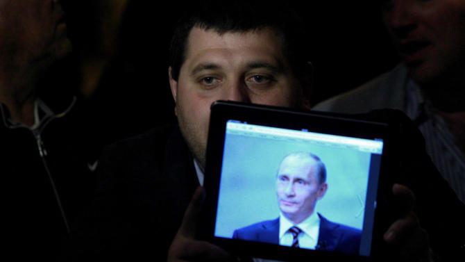 A man shows a picture of Russian President Vladimir Putin on a tablet during a protest from employees of Laiki Bank outside the Cypriot parliament in Nicosia, Cyprus, Thursday, March 21, 2013. Cypriot officials were scrambling Thursday to cement a revised plan to raise funds demanded by international creditors in exchange for an international bailout Thursday, with time running out fast and the country's economy just days away from potential ruin. (AP Photo/Petros Karadjias)