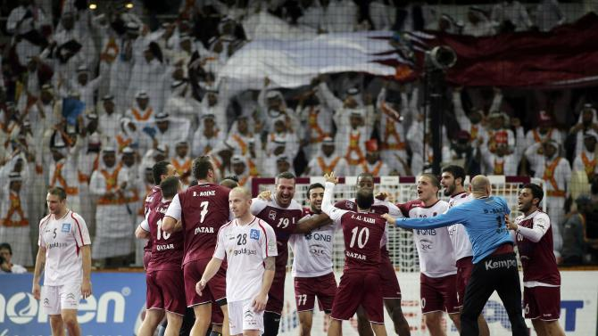 Qatar's players celebrate as Ziura and Weber of Austria walk after their round of 16 match of the 24th men's handball World Championship in Doha