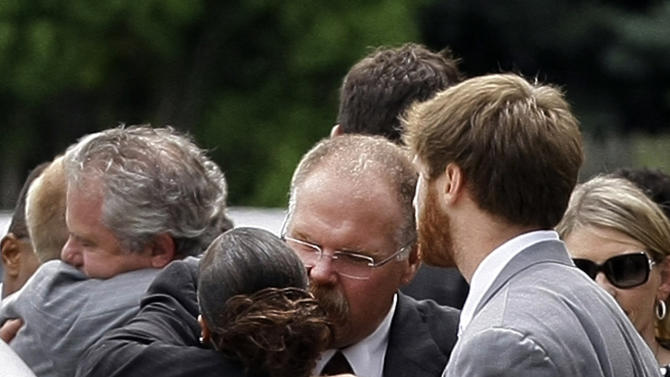 Philladephia Eagles coach Andy Reid, center, is embraced after the funeral for his son Garrett Reid, Tuesday, Aug. 7, 2012 in Broomall, Pa. Reid, 29, was found dead Sunday morning, Aug. 5, in a dorm room at the team's Lehigh University NFL football training camp. Looking on at right are his wife Tammy and son Britt. (AP Photo/Brynn Anderson)