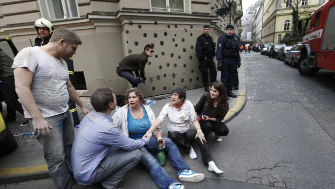 Injured people sit on a sidewalk after a explosion downtown Prague, Czech Republic, Monday, April 29, 2013. Police said a powerful explosion has damaged a building in the centre of the Czech capital and they believe some people are buried in the rubble. (AP Photo/Petr David Josek)