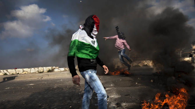 """Masked Palestinians clash with Israeli troops as they mark the """"Land Day"""" in the east Jerusalem neighborhood of Issawiyeh, Friday, March 30, 2012. Israeli security forces in riot gear Friday confronted Palestinian demonstrators, anticipating possible clashes along Israel's frontiers on """"Land Day"""". The """"Land Day"""" rallies are an annual event marked by Israeli Arabs and Palestinians in the West Bank and Gaza who protest what they say are discriminatory Israeli land policies. (AP Photo/Oded Balilty)"""