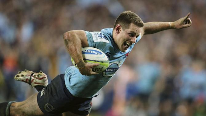 New South Wales Waratahs' Bernard Foley begins to celebrate just before scoring a try against the Brumbies during their Super Rugby semifinal match in Sydney, Saturday, July 26, 2014. The Waratahs won the match 26-8. (AP Photo/Rick Rycroft)