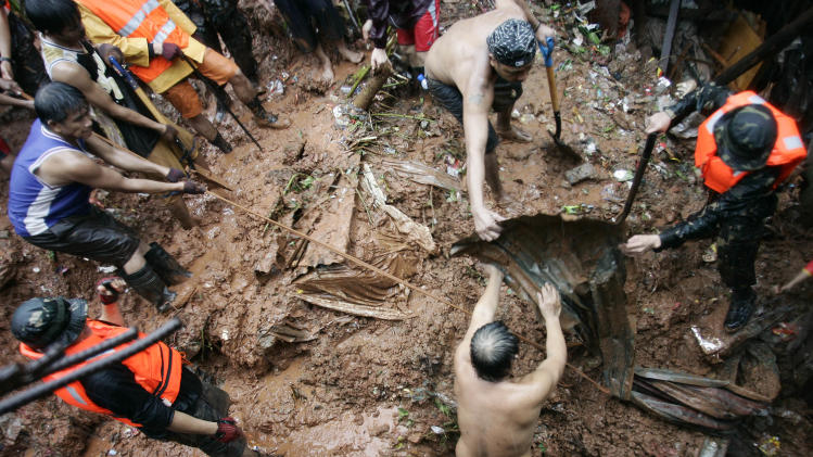 Filipino rescuers dig for survivors where four homes collapsed in a landslide incident in Quezon City, north of Manila, Philippines, on Tuesday Aug. 7, 2012. Relentless rains submerged half of the sprawling Philippine capital, triggered a landslide that killed eight people and sent emergency crews scrambling Tuesday to rescue and evacuate tens of thousands of residents. (AP Photo/Mike Alquinto)