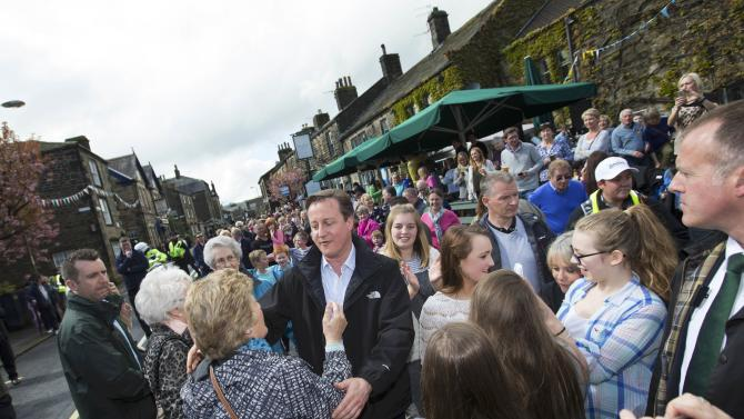Britain's Prime Minister David Cameron prepares to embrace a member of the public as he arrives to watch the Tour de Yorkshire cycle race pass through Addingham