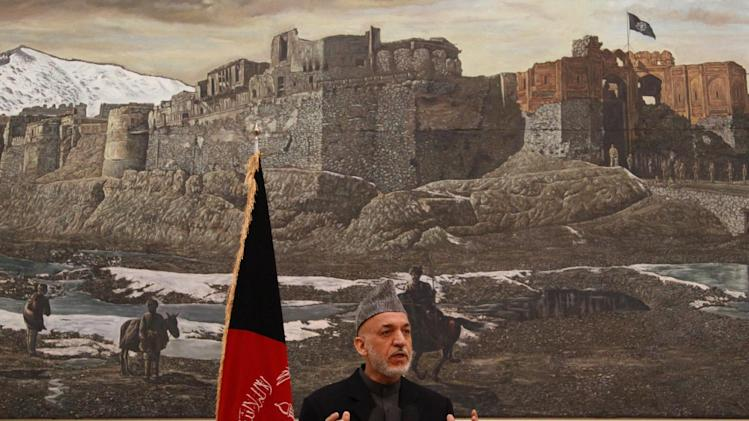 Standing behind a pairing depicting a battle between Russian and Afghan forces, the Afghan president Hamid Karzai makes a point during a press conference at the presidential palace in Kabul Afghanistan, Saturday, Dec. 8, 2012. Karzai said Saturday that Thursday's assassination attempt on the country's intelligence chief was planned in neighboring Pakistan but he did not provide any evidence to back up his claim, and was careful not to accuse the Pakistani government of having any role in the suicide attack. (AP Photo/Ahmad Jamshid)