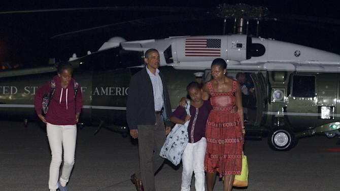 President Barack Obama, first lady Michelle Obama and their daughters Sasha and Malia walk from Marine One to board Air Force One, Friday, Aug. 26, 2011, at Cape Cod Coast Guard Air Station in Bourne, Mass., en route to Washington after a family vacation on Martha's Vineyard. Urging everyone in Hurricane Irene's path to get ready, President Barack Obama decided to cut his vacation short Friday and return to the White House for a storm he described as potentially historic. (AP Photo/Carolyn Kaster)