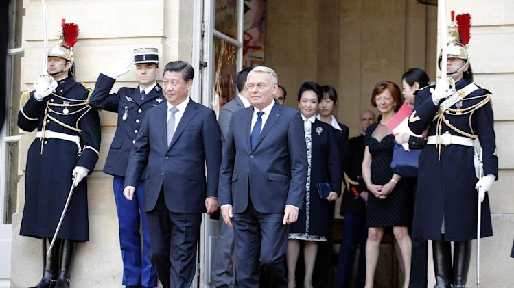 Chinese President Xi Jinping, centre left, and France's Prime Minister Jean Marc Ayrault, leave after a meeting in Paris, Thursday March 27, 2014. Deal-making and commemorations of a half-century of French diplomatic ties with Communist China were the order of business during Xi's three-day visit, part of his European tour. (AP Photo/Christophe Ena)