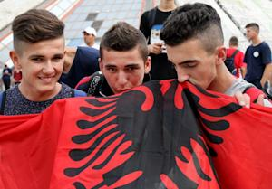 Football fans kiss the Albanian flag as they protest…