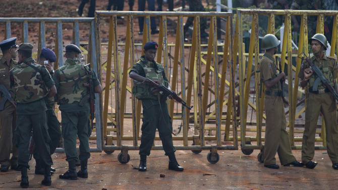 Army soldiers and police officers stand guard at the entrance of a prison in Colombo, Sri Lanka, Saturday, Nov. 10, 2012. A shootout between rioting prisoners and security forces at the prison killed 27 inmates, while police said Saturday that they arrested five prisoners who had managed to escape. (AP Photo/Gemunu Amarasinghe)