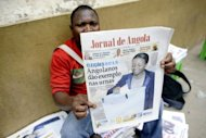 An Angolan newspaper street seller holds up a copy of the national paper in the street of Luanda on September 1. President Jose Eduardo dos Santos was poised to extend his 33-year rule, as his party took a hefty lead in this week's vote, despite frustrations among the poor at being left out of Angola's oil boom