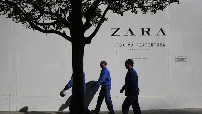 Workers walks past a Zara store closed for renovation in downtown Madrid