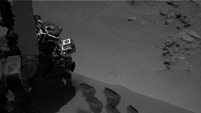 This image by NASA shows marks in the Martian soil made by the rover Curiosity. The space agency said the six-wheel rover is set to drive to a new destination soon. It landed in August on a two-year mission to study whether the environment is suitable for microbial life. (AP Photo/NASA)