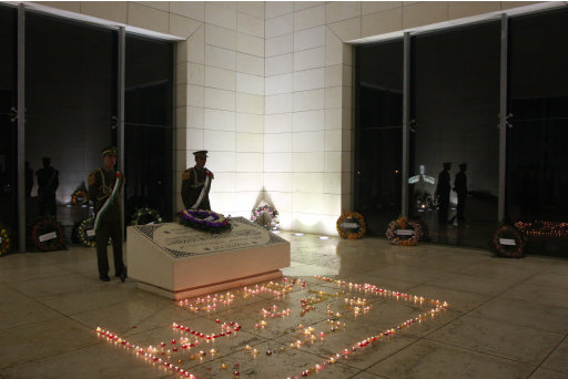 Palestinian guards stand near lit candles in the memorial to late Palestinian leader Yasser Arafat to mark the seventh anniversary of Arafat's death in the West Bank city of Ramallah, Thursday, Nov. 10, 2011. (AP Photo/Nasser Shiyoukhi)