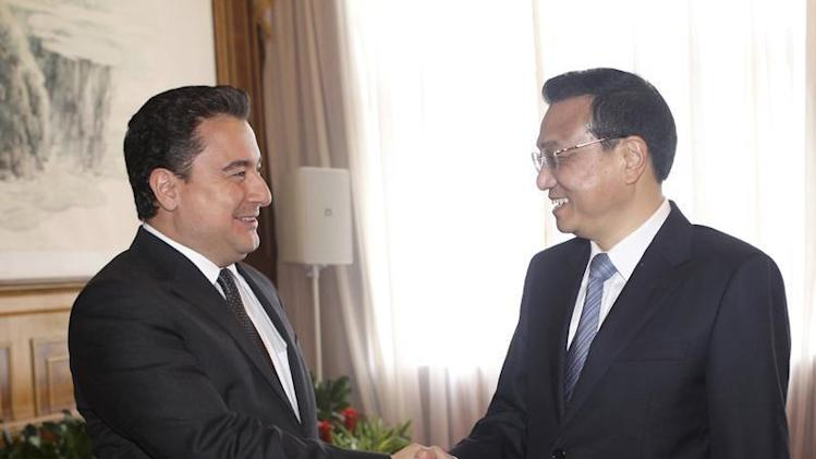 China's Premier Li Keqiang shakes hands with Turkey's Deputy Prime Minister Ali Babacan in Dalian