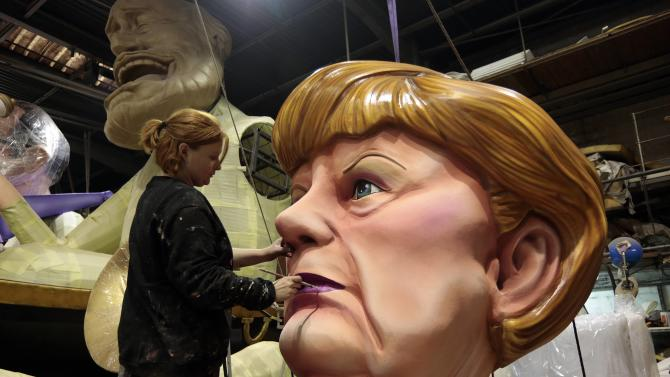 A worker puts the final touches on a giant figure of German Chancellor Angela Merkel during preparations for the carnival parade in Nice