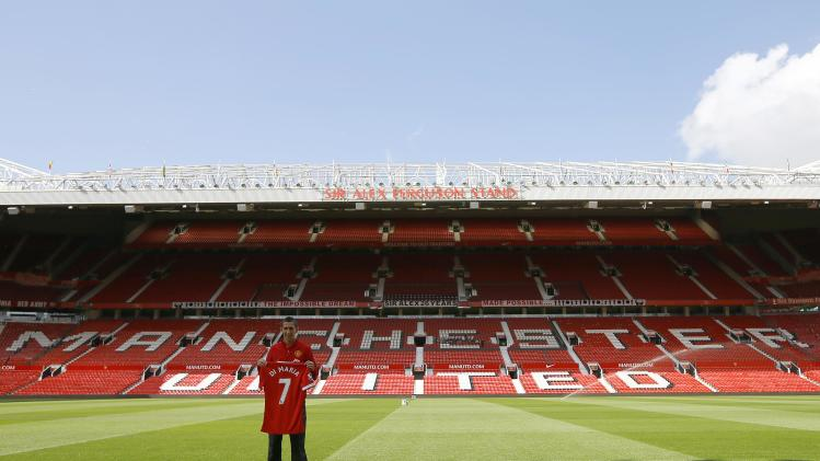 Manchester United's new signing Angel Di Maria poses for a photograph with his shirt at Old Trafford in Manchester