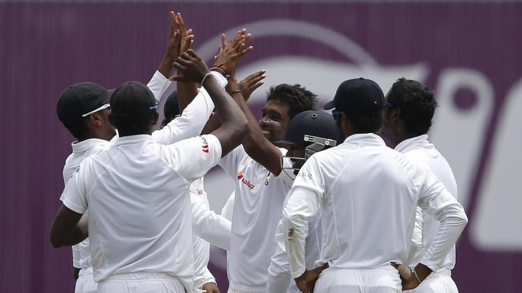 Sri Lanka's Perera celebrates with teammates after taking the wicket of South Africa's de Kock during the third day of their second test cricket match in Colombo